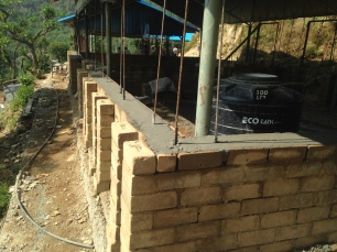The sill beam, poured with reinforced concrete. The blocks on this course are U-shaped and make a trough to allow for steel reinforcement to be placed inside the concrete.